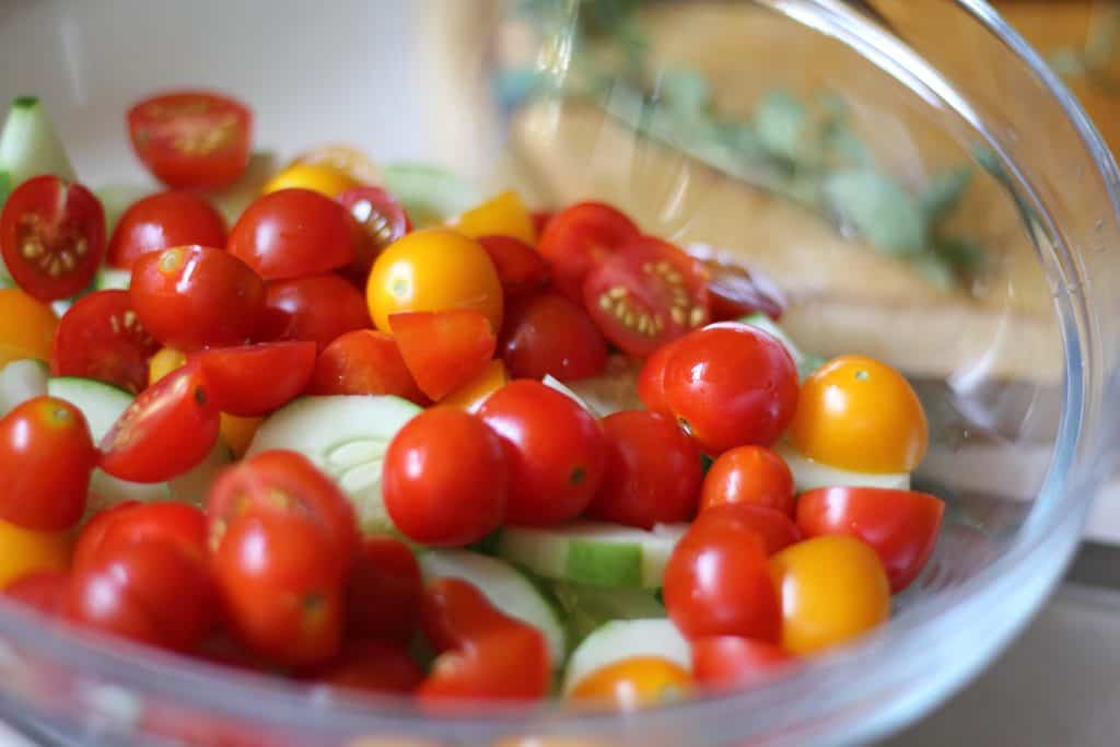sliced grape tomatoes and cucumbers in glass bowl