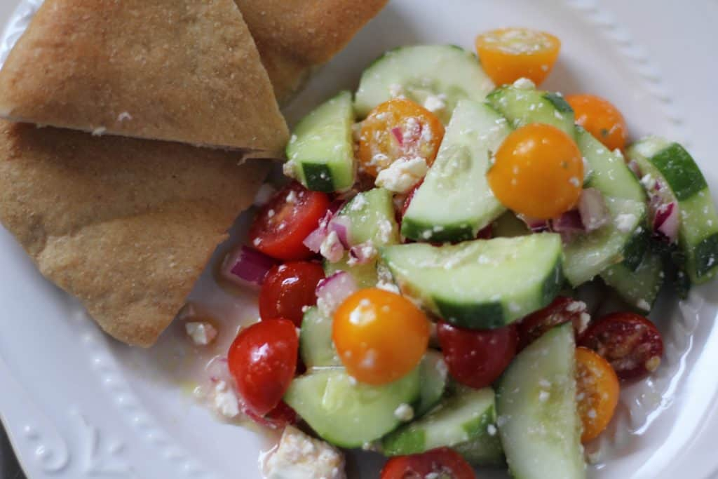 summer greek salad and pita on white plate