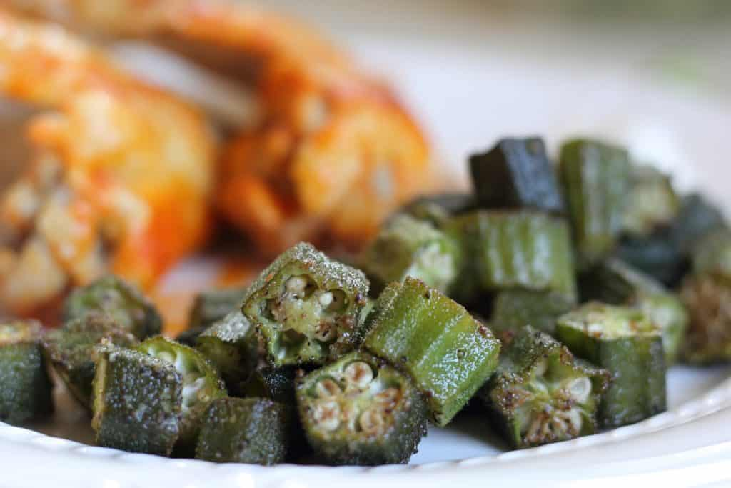 roasted okra on a white plate with chicken