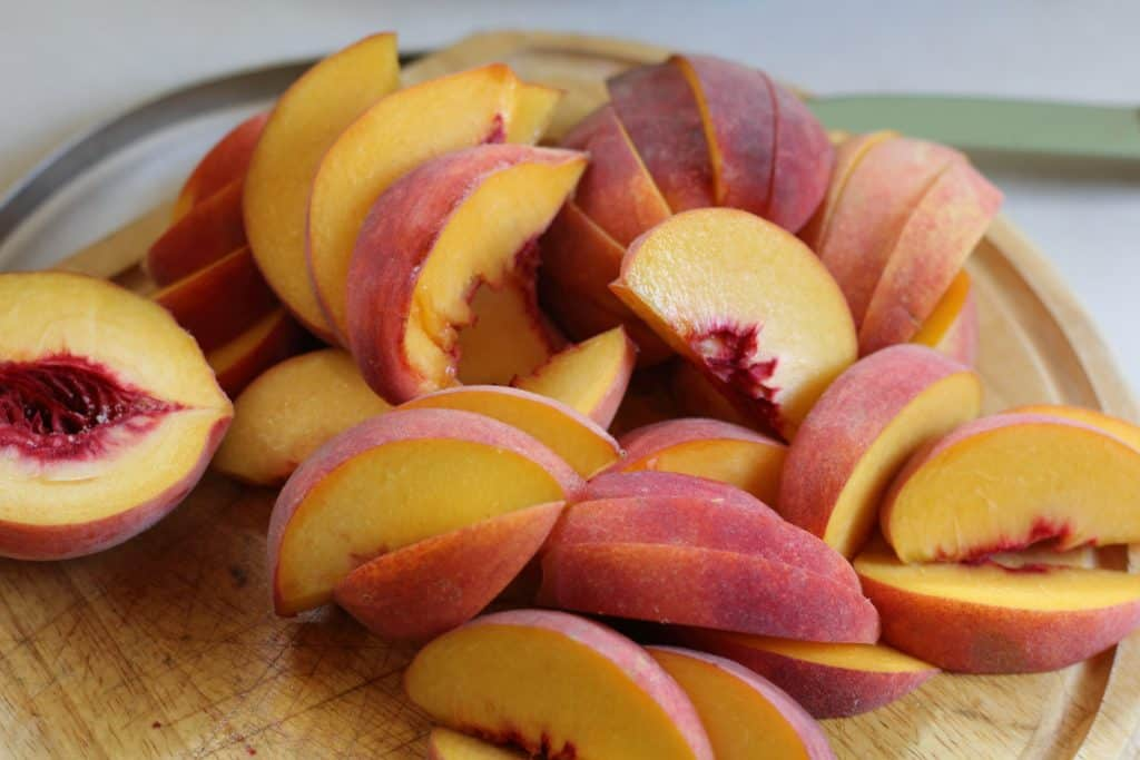 sliced peaches on a wooden cutting board