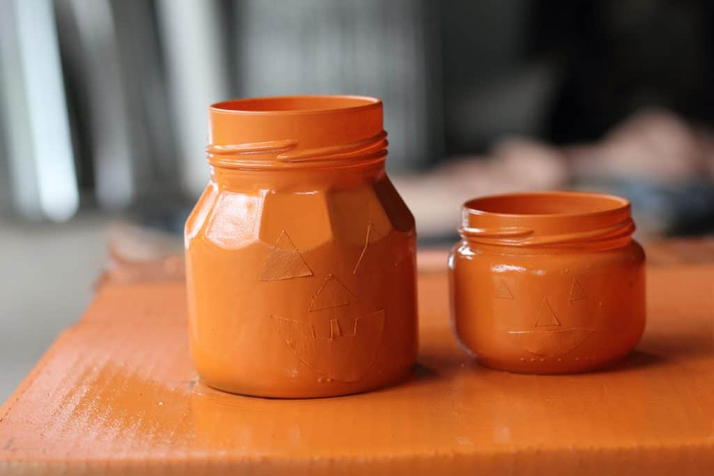 orange painted jars sitting on box