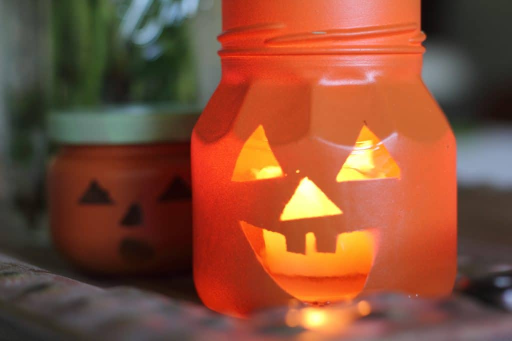 diy jack-o-lantern jar with lit candle inside