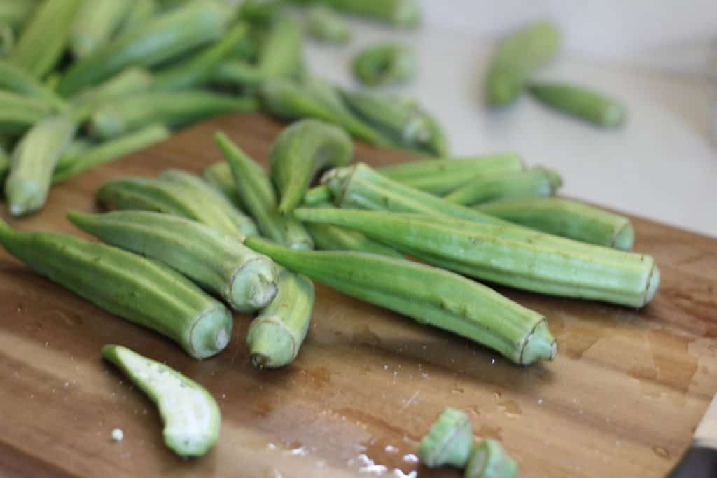 fresh okra pods on a wooden cutting board