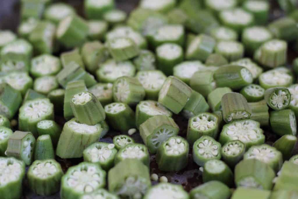 baked and sliced okra on a metal sheet pan