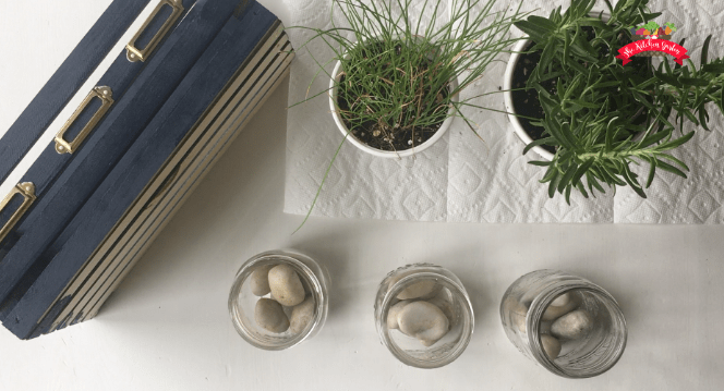 River rock in the bottom of mason jars for planting