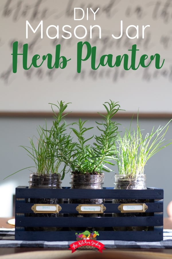 mason jars filled with chives and rosemary in a navy blue wooden crate with brass name plates