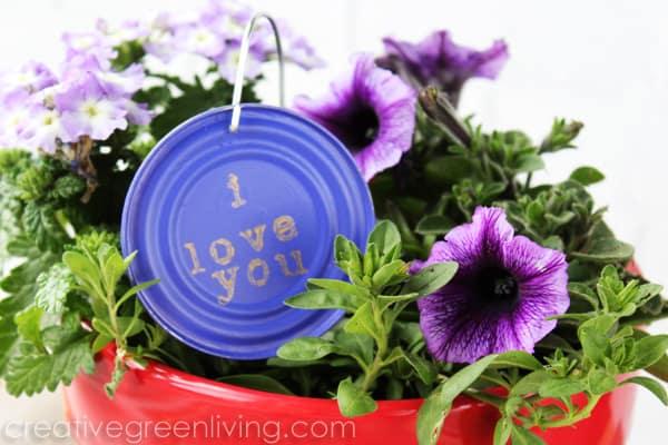 Purple garden marker hanging in a pot of petunias