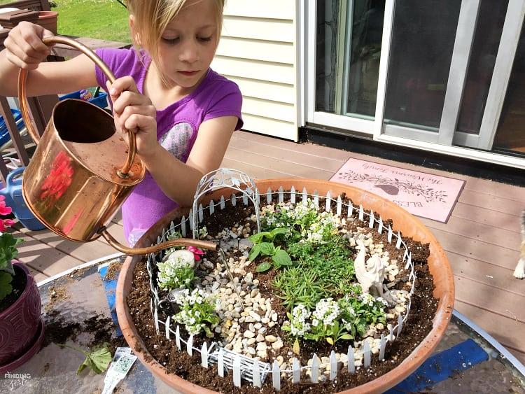 small girl watering a fairy garden in a clay pot