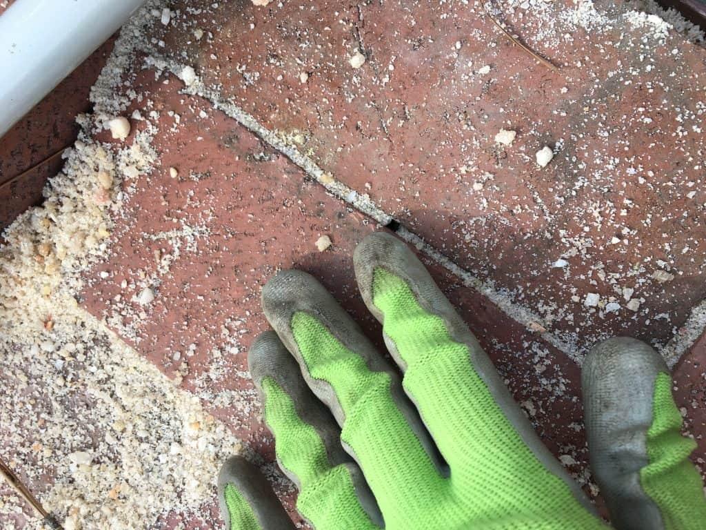 Sand being arranged between brick pavers