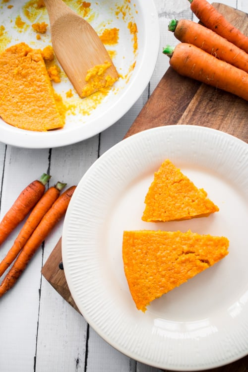 carrot souffle on a white plate with whole carrots beside it