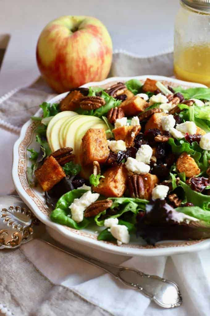 salad in a white bowl with sliced apples, roasted sweet potatoes, and toasted pecans