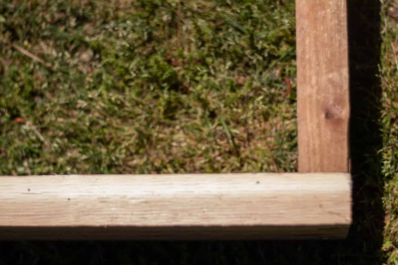 corner of a cedar raised garden bed sitting in the green grass