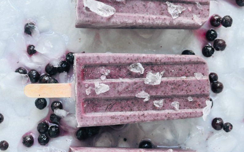Purple popsicles on a marble countertop with blueberries and ice around them.