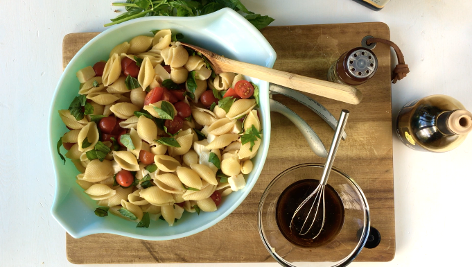 pasta, tomatoes, mozzarella, and basil in large bowl on wooden cutting board with dressing in a glass jar on the side