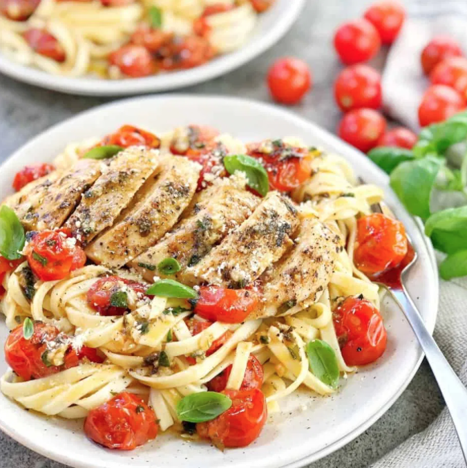 Linguini pasta on a white plate with cherry tomatoes, basil, and roasted chicken on top
