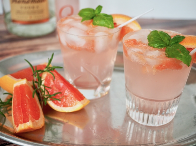 Two clear glasses of grapefruit basil vodka smash topped with basil sprigs on a silver tray