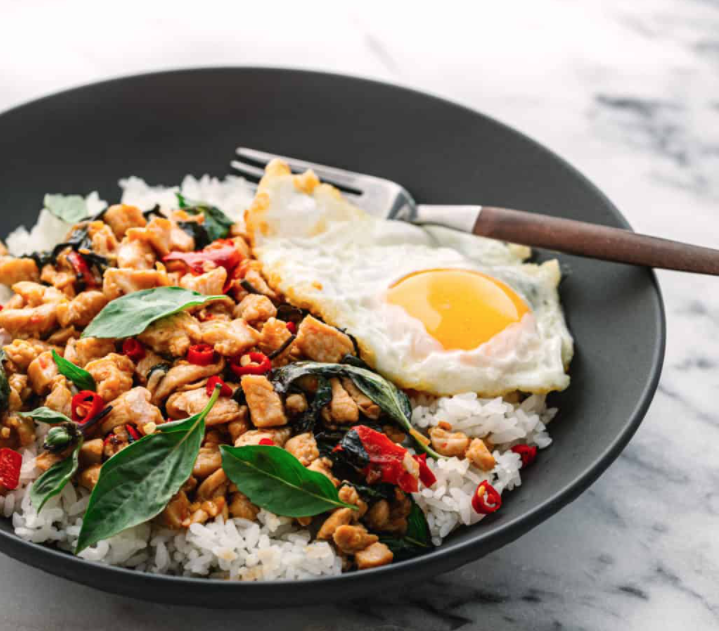 Black bowl with rice, spicy chicken, a fried egg, and fresh cut basil on top