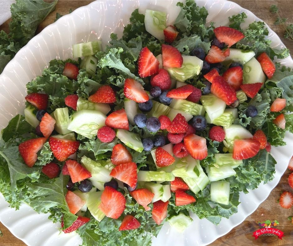berries and cucumbers on kale salad