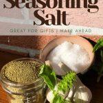 glass jar of seasoning salt on table with fresh garlic and basil