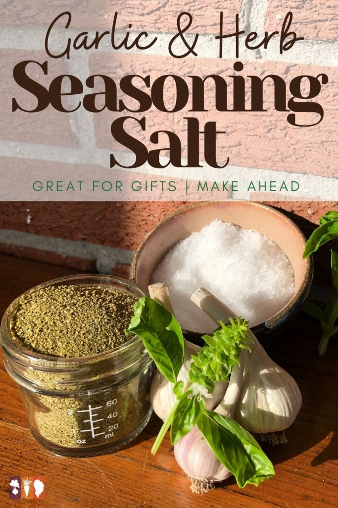 glass jar of seasoning salt on table with fresh garlic and basil
