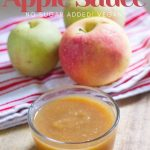 homemade applesauce in a glass jar with three apples behind