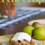 fresh pear crisp on a white plate topped with whipped cream