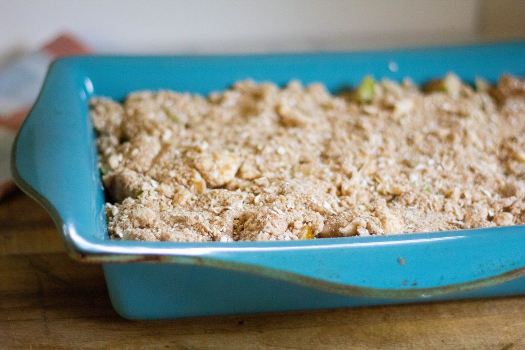 unbaked fresh pear crisp in a bright blue baking pan on wood counter.