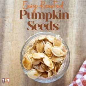 roasted pumpkin seeds in a glass jar on a wooden table