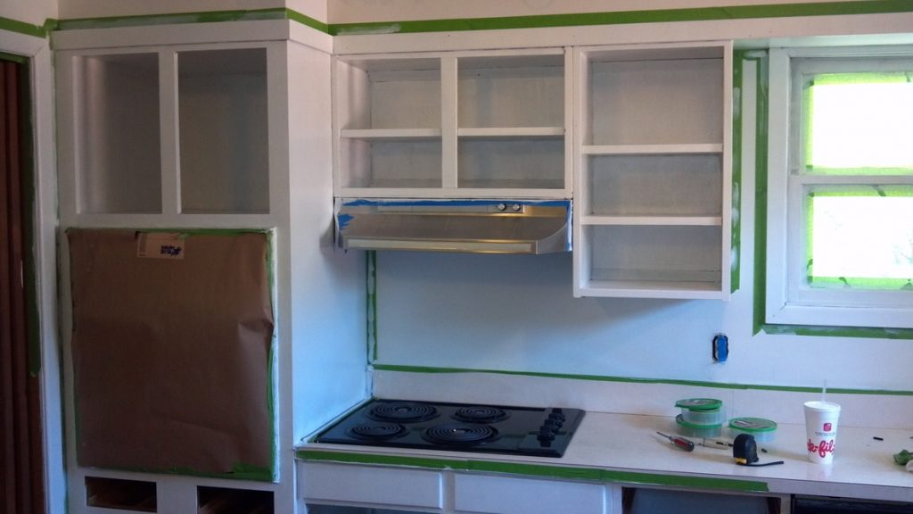 wood cabinets with doors removed being painted white